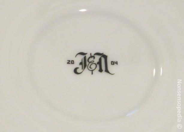 Tassen logo. J&N 2004, joka viittaisi kanavanrannan konseptiputiikin aukeamisvuoteen Suomessa