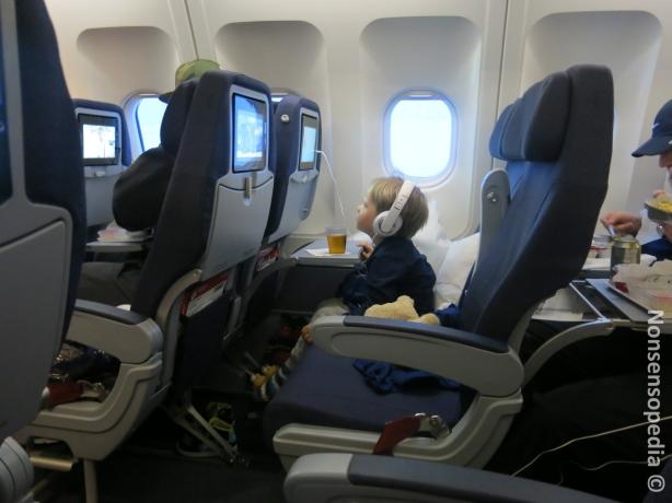 Pieni lentokoneessa katselee leffojaan