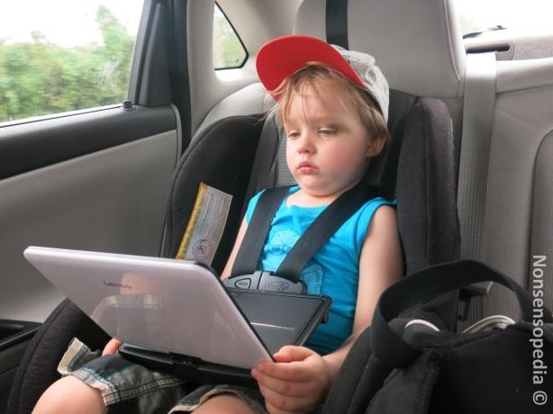 L väsyneenä tuijottaa Akua kannettavalta DVD-soittimelta